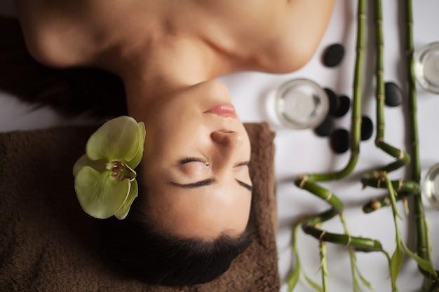 Jovem mulher bonita no spa recebe uma massagem facial