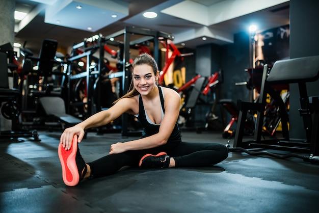 Jovem mulher bonita no sportswear que estica no gym, sorrindo na câmera.