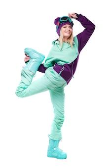 Jovem mulher bonita no terno de esqui roxo e botas de neve azul