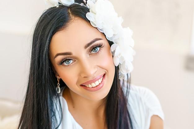 Jovem mulher bonita no vestido branco luxuoso. atirando em um estúdio branco.