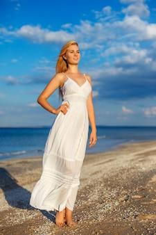 Jovem mulher bonita no vestido branco pelo mar no sol.