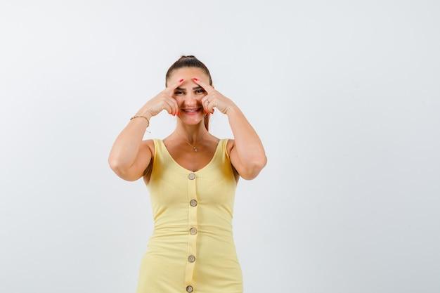 Jovem mulher bonita no vestido olhando por entre os dedos e olhando alegre, vista frontal.