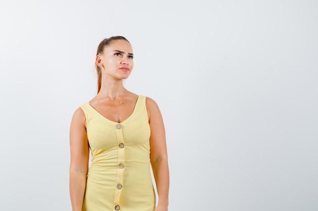 Jovem mulher bonita no vestido posando enquanto olhando para longe e olhando pensativa, vista frontal.