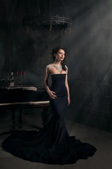 Jovem mulher bonita no vestido preto ao lado de um piano com velas dos candelabros e vinho, atmosfera dramática escura do castelo. boémia