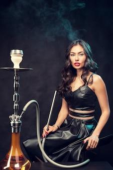 Jovem mulher bonita no vestido preto, fumar e exala o cachimbo de água
