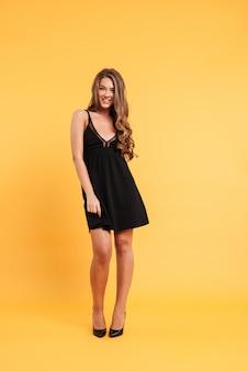 Jovem mulher bonita no vestido preto que está isolado sobre o amarelo e o levantamento. olhando a câmera.