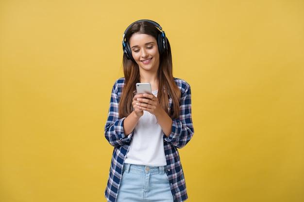 Jovem mulher bonita nos fones de ouvido que escuta a música e que dança no fundo amarelo.