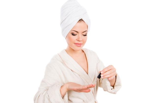 Jovem mulher bonita num roupão de banho pintando as unhas
