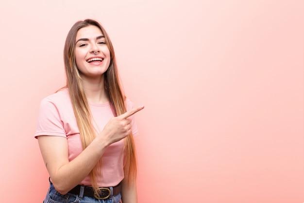Jovem mulher bonita olhando animado e surpreso apontando para o lado e para cima para copiar o espaço contra a parede rosa
