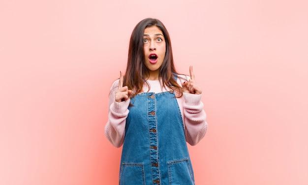 Jovem mulher bonita olhando chocado, espantado e boca aberta, apontando para cima com as duas mãos para copiar o espaço contra rosa