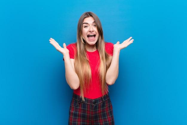 Jovem mulher bonita olhando feliz e animado, chocado com uma surpresa inesperada com as duas mãos abertas ao lado do rosto contra a parede azul