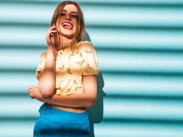 Jovem mulher bonita olhando. menina na moda em roupas de verão casual amarelo camiseta. e mostrando a língua