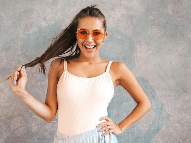 Jovem mulher bonita olhando. menina na moda em verão casual vestido e óculos de sol.