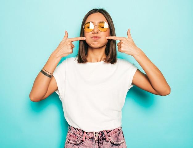 Jovem mulher bonita olhando para a câmera. menina na moda casual verão branco camiseta e jeans shorts em óculos de sol redondos. fêmea positiva mostra emoções faciais. modelo engraçado soprando as bochechas.