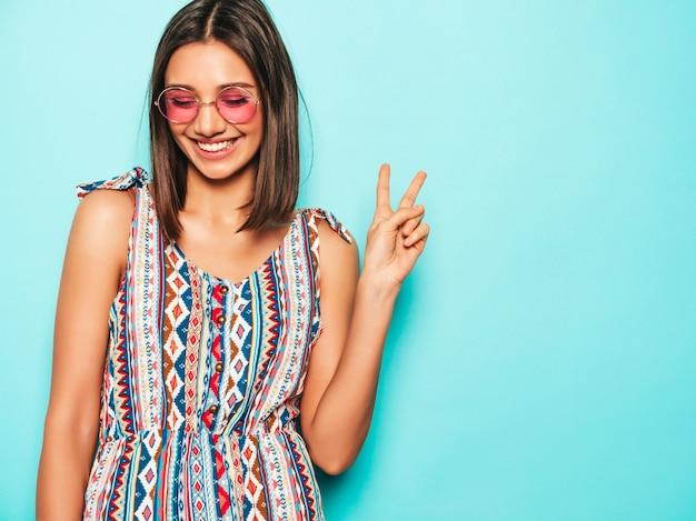 Jovem mulher bonita olhando para a câmera. menina na moda casual verão vestido e óculos de sol redondos. fêmea positiva mostra emoções faciais. modelo engraçado isolado em azul