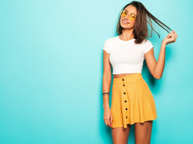 Jovem mulher bonita olhando para a câmera. menina na moda em camiseta casual verão branco e saia amarela em óculos de sol redondos. fêmea positiva mostra emoções faciais. modelo engraçado isolado em azul