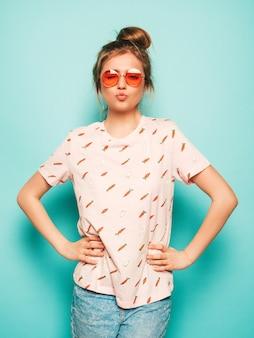 Jovem mulher bonita olhando para a câmera. menina na moda em roupas de verão casual camiseta faz cara de pato. fêmea positiva mostra emoções faciais. modelo engraçado isolado no azul em óculos de sol