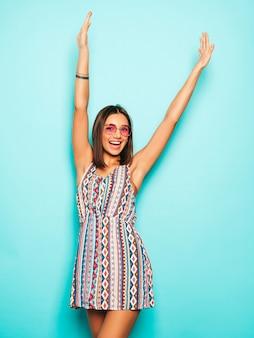 Jovem mulher bonita olhando para a câmera. menina na moda em vestido de verão casual e óculos de sol redondos. fêmea positiva mostra emoções faciais. modelo levantando as mãos e comemorando