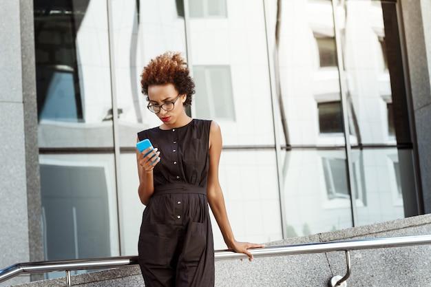 Jovem mulher bonita olhando para o telefone andando pela cidade