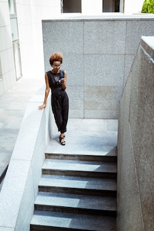 Jovem mulher bonita olhando para o telefone descendo escadas