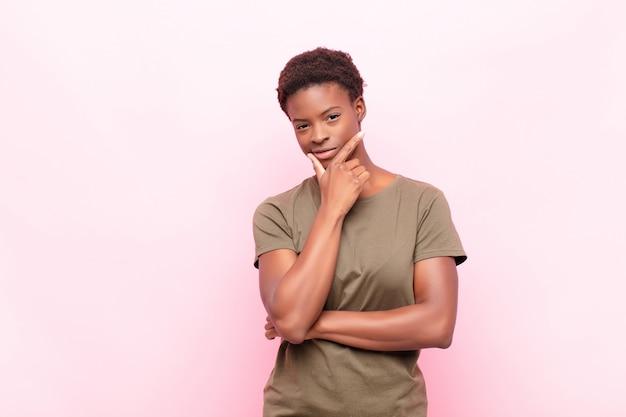 Jovem mulher bonita olhando sério, pensativo e desconfiado, com um braço cruzado e mão no queixo, opções de ponderação sobre parede rosa