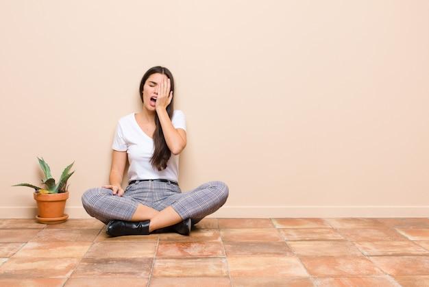 Jovem mulher bonita olhando sonolenta, entediada e bocejando, com dor de cabeça e uma mão cobrindo metade do rosto, sentado no chão