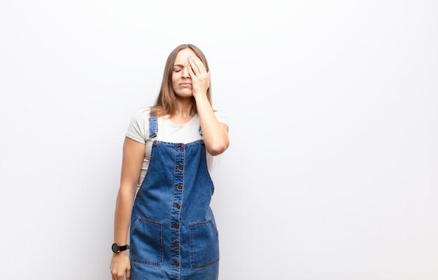 Jovem mulher bonita olhando sonolento, entediado e bocejando, com dor de cabeça e uma mão cobrindo metade do rosto contra a parede branca
