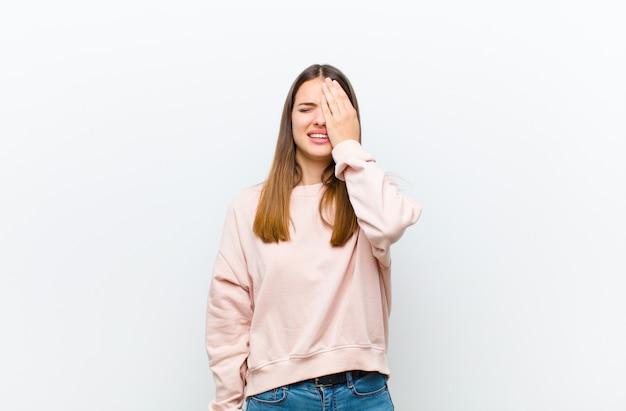 Jovem mulher bonita olhando sonolento, entediado e bocejando, com dor de cabeça e uma mão cobrindo metade do rosto sobre a parede branca