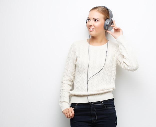 Jovem mulher bonita ouvindo a música dos fones de ouvido