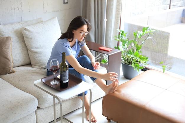 Jovem mulher bonita pintando as unhas com verniz, sentada no sofá aconchegante. Foto Premium