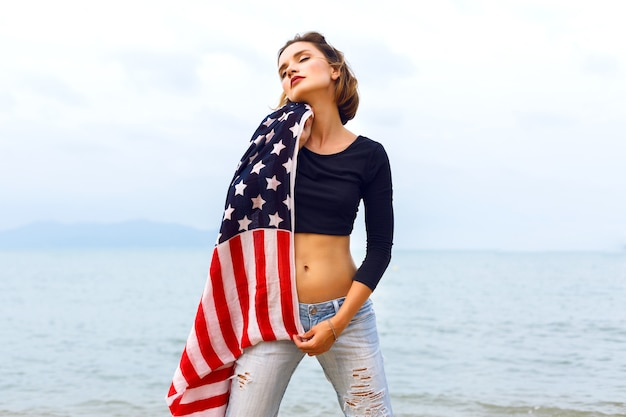 Jovem mulher bonita posando à beira-mar