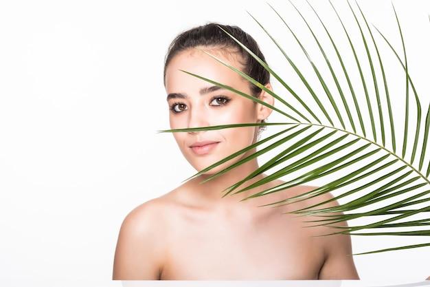 Jovem mulher bonita posando com folha de palmeira verde