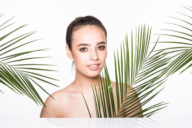 Jovem mulher bonita posando com folhas de palmeira verde