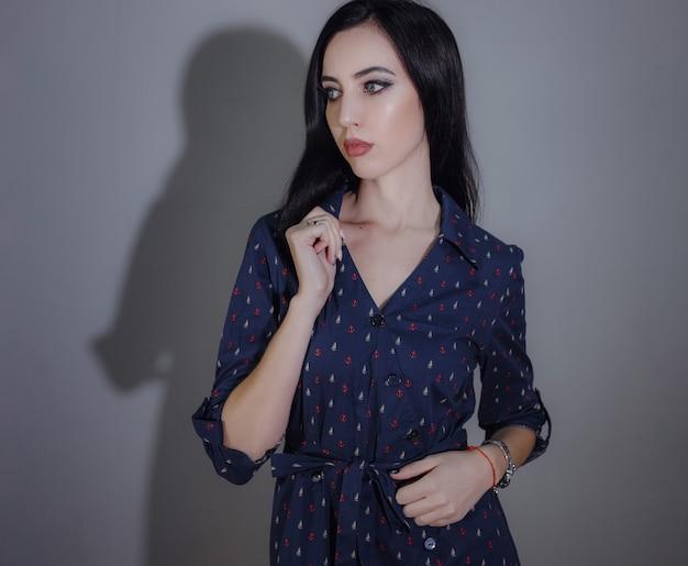 Jovem mulher bonita posando em cinza em vestidos diferentes. escolhe a melhor opção para uma noite de feriado