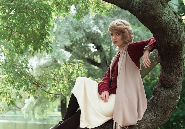 Jovem mulher bonita posando em uma árvore.