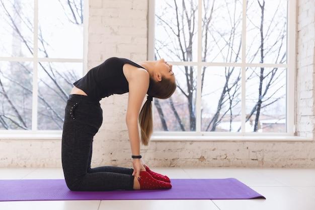 Jovem mulher bonita praticando ioga perto da janela