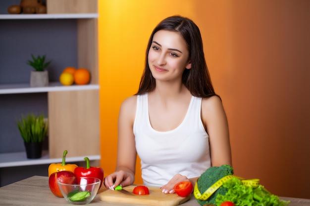 Jovem mulher bonita prepara uma salada de dieta útil