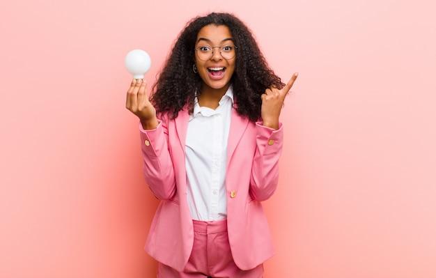 Jovem mulher bonita preta com uma lâmpada, tendo uma idéia contra a parede rosa