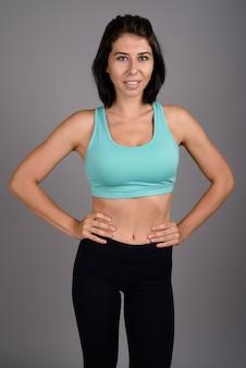 Jovem mulher bonita pronta para ginásio contra fundo cinza