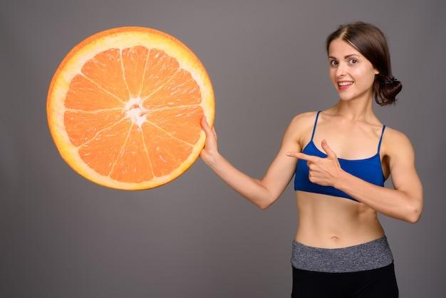 Jovem mulher bonita pronta para ginásio contra parede cinza