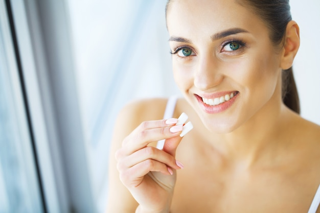Jovem mulher bonita que come a goma de mastigação, sorrindo