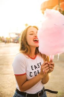 Jovem mulher bonita que come o algodão doce cor-de-rosa