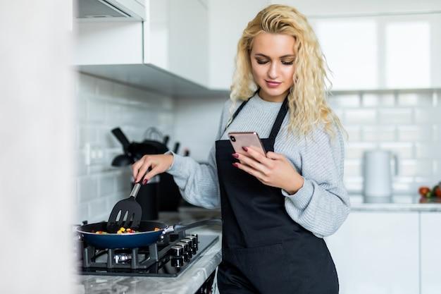 Jovem mulher bonita que cozinha o jantar saudável usando a frigideira, usando o telefone celular na cozinha