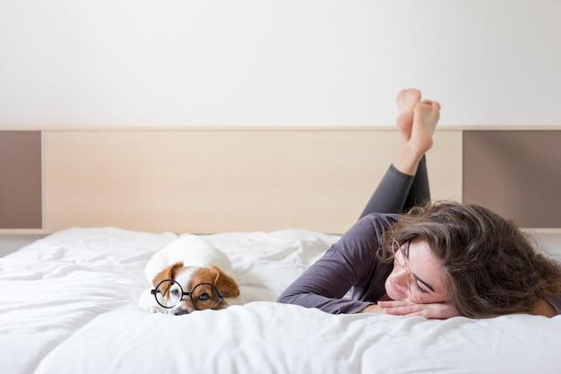 Jovem mulher bonita que encontra-se na cama com seu cão pequeno bonito além. casa, ambiente interno e estilo de vida