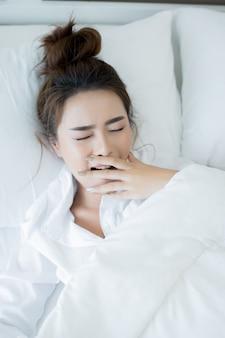 Jovem mulher bonita que encontra-se para baixo na cama e no sono.
