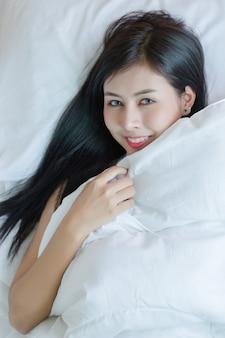 Jovem mulher bonita que encontra-se para baixo na cama.