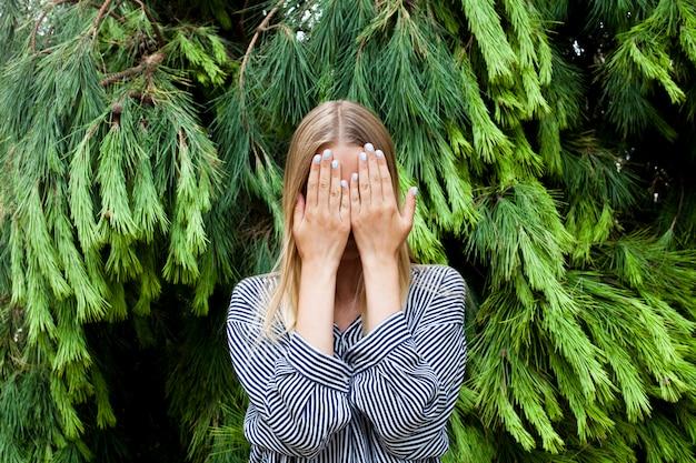 Jovem mulher bonita que esconde sua cara que está na floresta contra abeto.