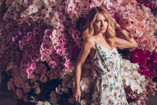 Jovem mulher bonita que está na frente das flores bonitas da orquídea