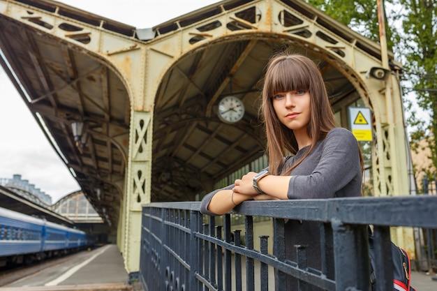 Jovem mulher bonita que está na plataforma do conceito do curso da estação de trem.