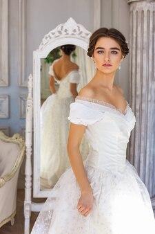 Jovem mulher bonita que está no vestido branco perto do espelho.